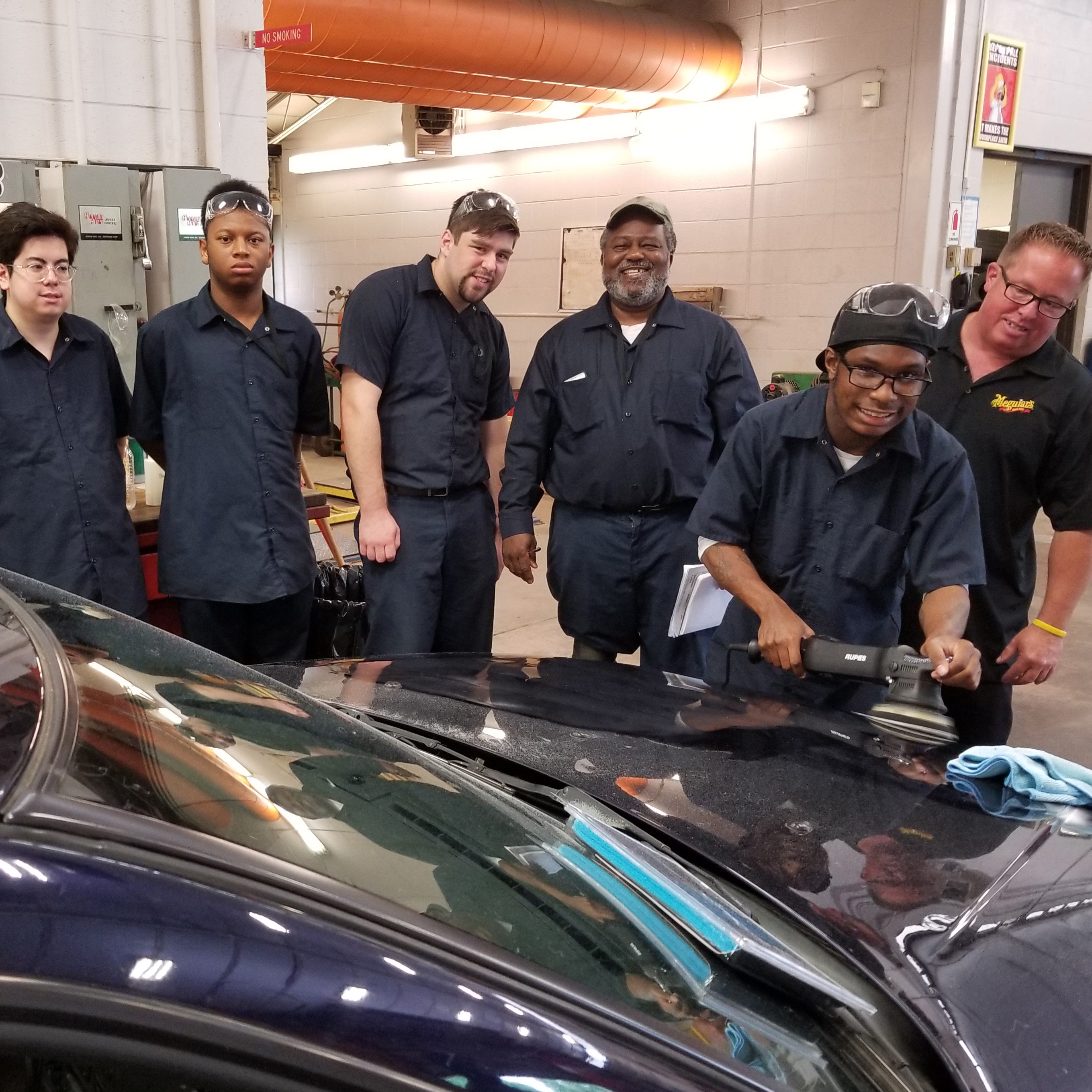 Four Automotive Detailing students watch as one student learns to buff a car hood, as shown by a Mequiars' Car Care expert.