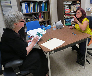 Two women sitting at a table; one woman writing on a clipboard and the other woman is talking with ASL.