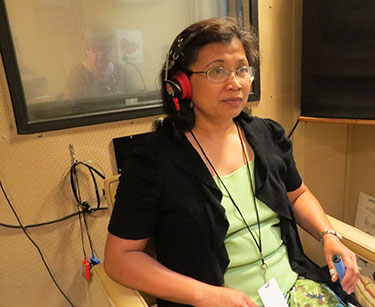 A woman with headphones on and a corded stick in her hand, behind her a woman sits behind a window at a microphone.