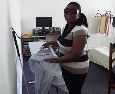 A woman ironing a shirt. She is wearing dark glasses and a white cane leans against the wall nearby.