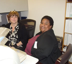 Two women sitting at a desk in an office.