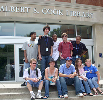 A group of ten high school age people on the steps of the Albert S. Cook Library.
