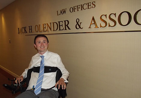 Josh sitting in the hallway in front of his employer's sign: Law Offices, Jack H. Olender & Associates.