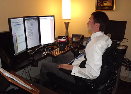 Josh at his desk with assorted assistive technology, including: three legal-size computer screens and a drinking cup holder.