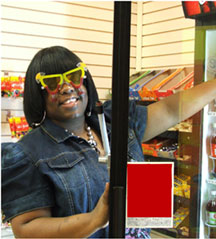 A woman standing in a store, opening a refrigerator case door.