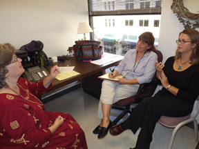 Three women sitting in an office. Two of the women are talking using ASL, the third is taking notes.