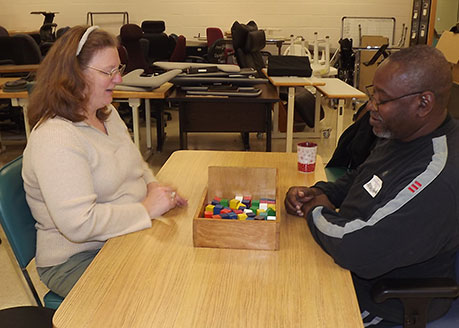 A man and a woman sitting at a table looking at a box of colored wooden blocks.