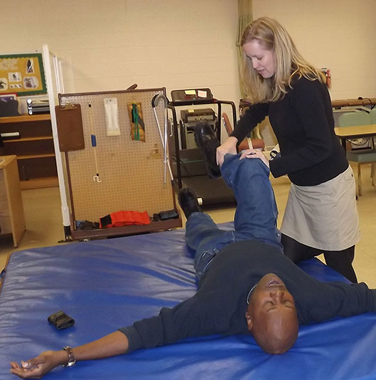 A man lying on a cushioned table while a woman stands next to him and bends his leg.
