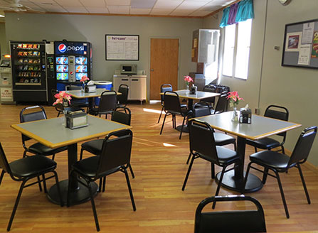 A room with soda and snack machines, and several small table, each with four chairs.