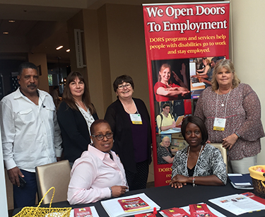 Six of DORS' business services representatives at a DORS table at an outreach event.