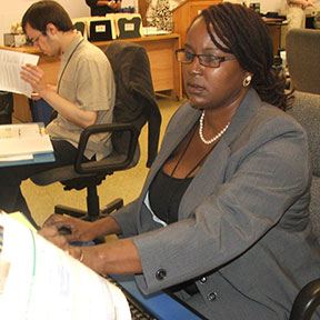 A woman sits working at a computer. Beside her, a man is consulting a text book.