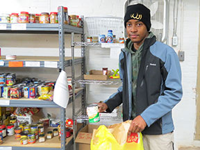 A young man packs canned goods into a bag.