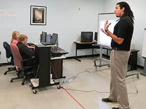 A man lectures at the front of classroom where the students are using computers.