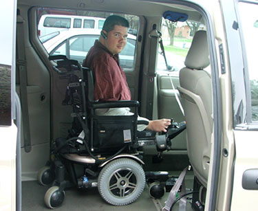 A young man who does not have arms, in a wheelchair, inside a minivan.