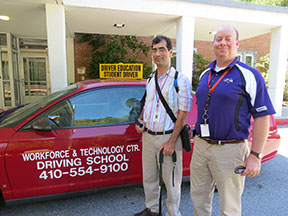 Two men stand next to a car.  On the side of the car are the words Workforce & Technology Center Driving School 410-554-9100. A sign on the roof says Driver Education Student Driver.