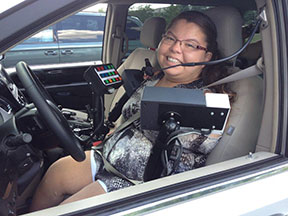 A young woman in the driver's seat of a heavily modified minivan.
