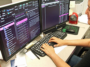A woman types on a keyboard. In front of her are two oversized monitors displaying enlarged text in high contrast.
