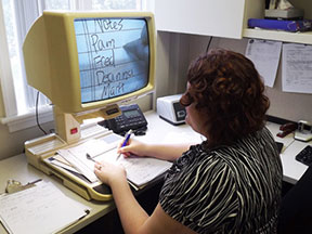A woman is writing a list of names with the help of a CCTV video display.