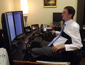 A man in a wheelchair has oversized monitors as well as a telescopic microphone and cupholder.
