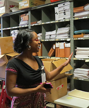 A woman points out stacks of documents in a filing room.