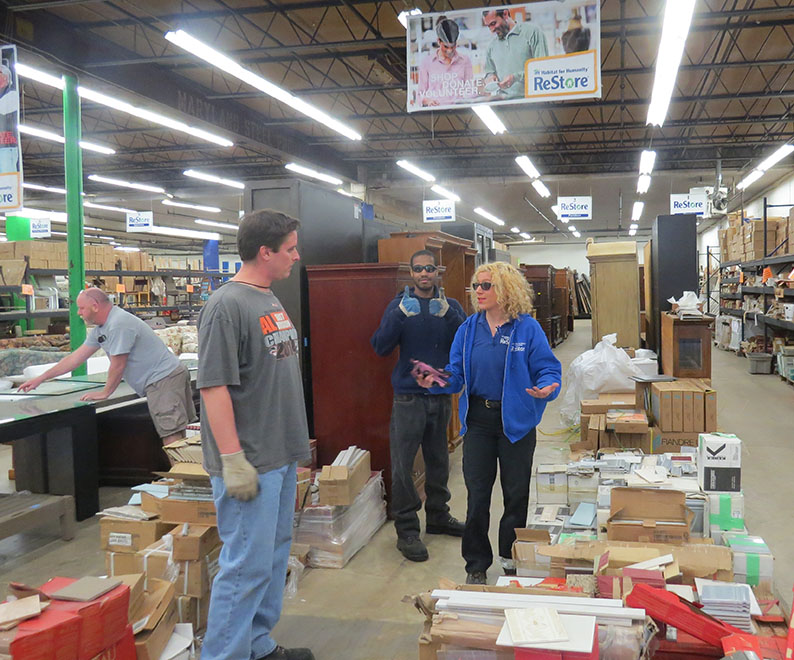 Three men and a woman in a ReStore store. The woman is giving one of them instructions on moving some boxes.