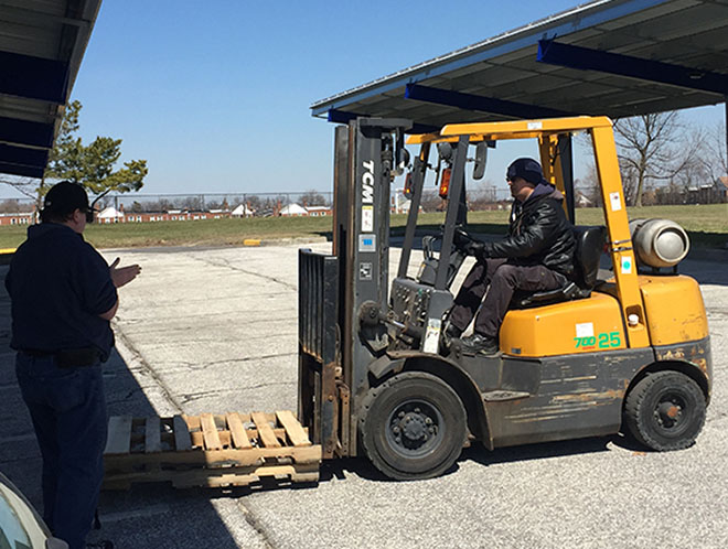 A man giving another man directions on how to drive a forklift.