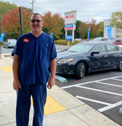 Luke stands outside a CVS pharmacy, wearing a Pharmacy Tech uniform.