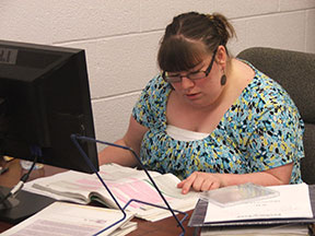 A woman seated at a computer studies a textbook.