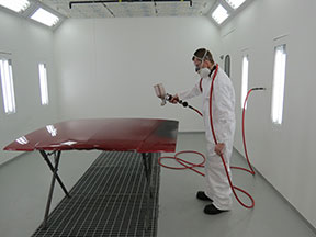 A man in a respirator and white coveralls spray paints a car hood in a body shop paint booth.