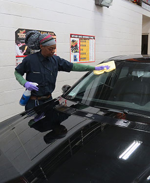 A student cleans a car windshield.
