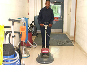 A man polishes a hallway floor with a buffing machine.
