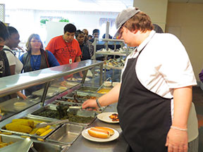 A man dishes out food to students waiting in a cafeteria line.