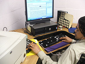 A man at a computer edits a Word document.