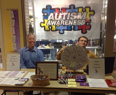 Two men sitting at a table with papers on it and an Autism Awareness banner behind them.