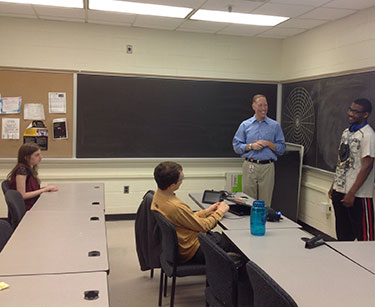 Three students and an instructor in a classroom. Two students are seated; the instructor and a student are standing.