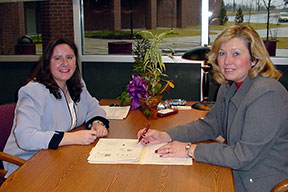 Two women sit on either side of desk in a school office.