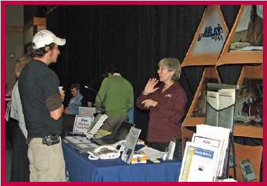 A man and a woman at a conference exhibit table.