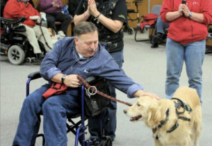 A man in a wheelchair pets his service dog.