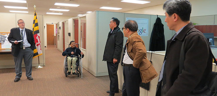 Five men in a office area. One man talks and the others lister. The man in the center is in a wheelchair and holds a white cane.